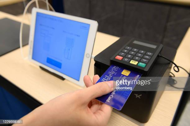 An employee demonstrates using a reception device during a media event at a branch of Mizuho Bank Ltd. In Kawasaki, Kanagawa Prefecture, Japan, on...