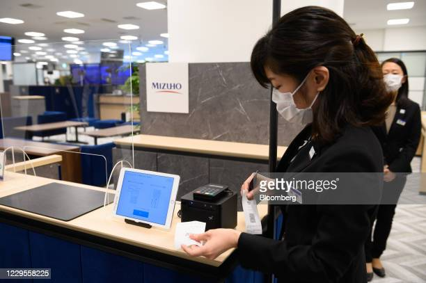 An employee demonstrates using a reception ticketing device during a media event at a branch of Mizuho Bank Ltd. In Kawasaki, Kanagawa Prefecture,...