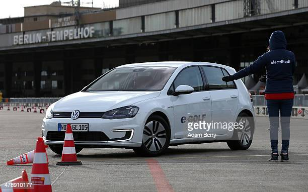 An employee directs a visitor driving an electric Volkswagen e-Golf automobile at the Electric Mobility Week , a public Volkswagen event at the...