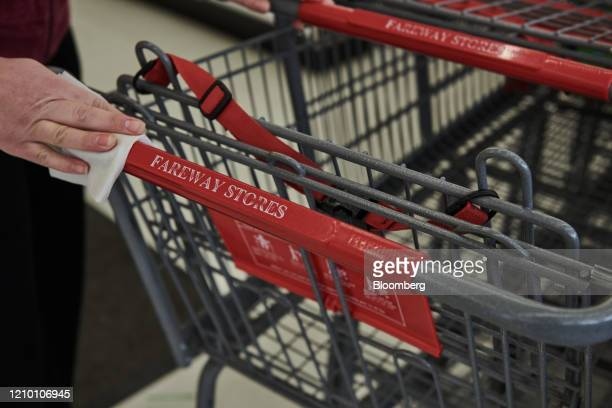 An employee disinfects a shopping cart at a Fareway grocery store in Sioux Falls South Dakota US on Wednesday April 15 2020 South Dakota Governor...