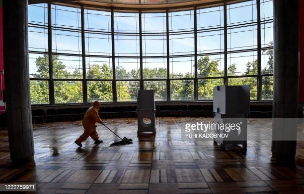 An employee disinfects the floor around voting booths at a polling station in Moscow on June 25, 2020. - Russians were casting early ballots on June...