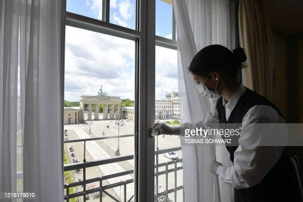 An employee disinfects the window handle of a suite with a view on landmark Brandenburg Gate of Berlin's famous Hotel Adlon Kempinski on May 26 one...