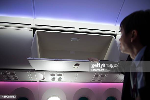 An employee display an overhead compartment on board a Boeing Co 787 Dreamliner aircraft operated by Qatar Airways Ltd at the Singapore Airshow held...