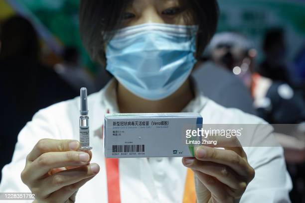 An employee displaying a coronavirus vaccine candidate from China National Biotec Group , during the 2020 China International Fair for Trade in...