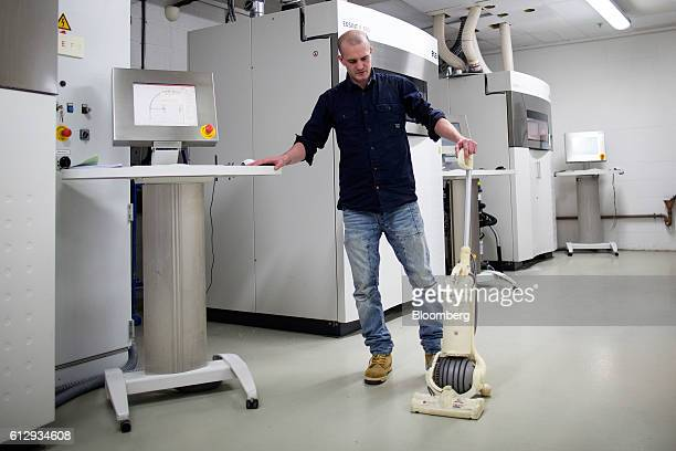 An employee displays a 3D printed version of the Dyson DC24 vacuum cleaner at the 3D Printing Lab inside the Dyson Ltd campus in Malmesbury UK on...