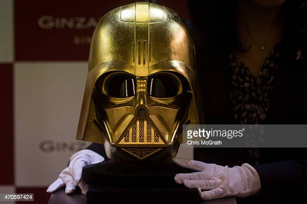 An employee displays a Darth Vader mask covered in gold leaf at Ginza Tanaka jeweler on April 22 2015 in Tokyo Japan To celebrate the release of the...