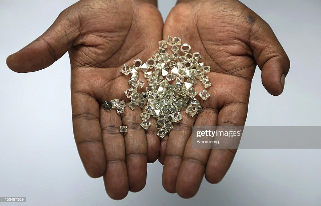 An employee displays a handful of uncut diamonds in this arranged photograph at DTC Botswana, a unit of De Beers, in Gaborone, Botswana, on Thursday, Oct. 25, 2012. De Beers, the biggest diamond producer by revenue, is moving the sorting and trading of rough stones to Botswana from London to secure access to the world's largest supplier of diamonds by value and challenge Antwerp's dominance as the world's biggest trading hub for rough diamonds. Photographer: Chris Ratcliffe/Bloomberg via Getty Images