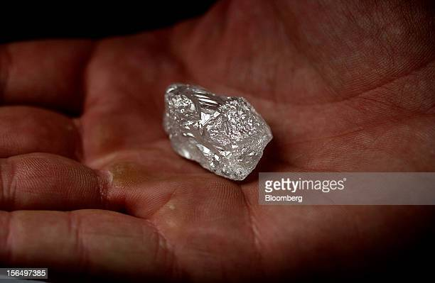 An employee displays a large uncut diamond in this arranged photograph at DTC Botswana a unit of De Beers in Gaborone Botswana on Thursday Oct 25...