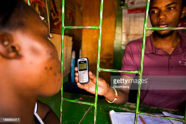 An employee displays a Nokia 1200 mobile phone to a resident as they transfer money using the MPesa banking service in Nairobi Kenya on Sunday April...