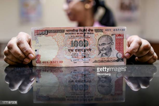 An employee displays an Indian onethousand rupee banknote for a photograph at a branch of the HDFC Bank Ltd in Mumbai India on Thursday Aug 22 2013...