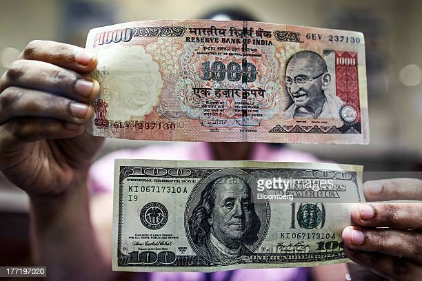 An employee displays an Indian onethousand rupee banknote top and a US onehundred dollar banknote for a photograph at a branch of the HDFC Bank Ltd...