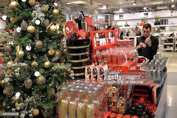 An employee displays goods next to a Christmas tree on December 18 2014 at the Printemps department store in Paris AFP PHOTO / STEPHANE DE SAKUTIN
