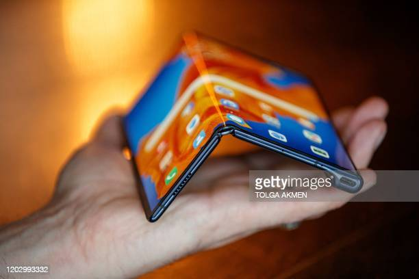 An employee displays the Huawei Mate Xs to the media during a photocall for the launch of the new foldable smartphone in London on February 18, 2020....