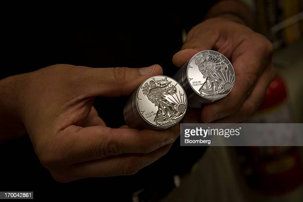 An employee displays two finished coin dies at the United States Mint at West Point in West Point New York US on Wednesday June 5 2013 Sales of gold...