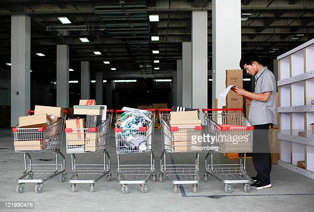 An employee double checks shopping carts filled with items placed from orders at the Yihaodian warehouse in Shanghai China on Tuesday Aug 23 2011...