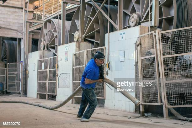 An employee drags a hose through the ball mill department at the Shabbir Tiles Ceramics Ltd production facility in Karachi Pakistan on Wednesday Dec...
