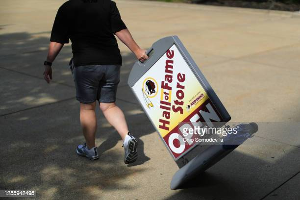 An employee drags a sign out in front of the Hall of Fame Store at FedEx Field home of the NFL's Washington Redskins team July 13 2020 in Landover...