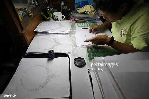 An employee draws designs for necklaces at the Myanmar VES Joint Venture Co gems and jewelry workshop in Yangon Myanmar on Monday June 3 2013...