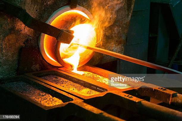 An employee draws molten gold from a furnace into a mould during the final stage of the refining process at the Kaloti Jewellery LLC factory in...