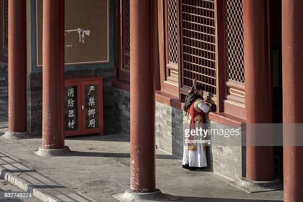An employee dressed in a Qing Dynasty costume stands near a window inside the Palace Museum at the Forbidden City in Beijing China on Thursday Nov 24...