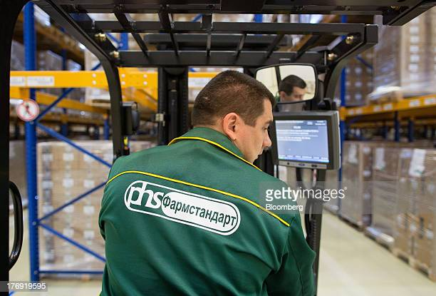 An employee drives a forklift truck around the storage facility at OAO Pharmstandard's Leksredstva drug manufacturing unit in Kursk Russia on Friday...