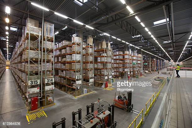 An employee drives a forklift truck past storage aisles containing retail goods for shipping in the Ikea AB distribution center in Yesipovo village...