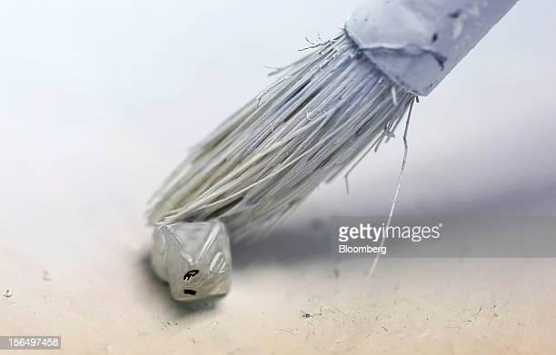 An employee dusts a diamond with powder before xraying at the Shrenuj Botswana Ltd sightholder office in Gaborone Botswana on Thursday Oct 25 2012 De...