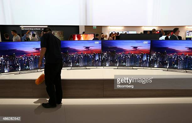 An employee dusts Sony 4K televisions as they sit on display at the Sony Corp exhibition stand during previews of the IFA International Consumer...