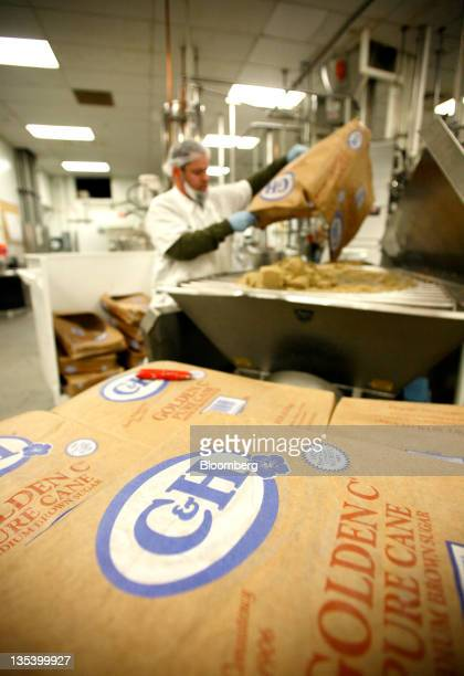 An employee empties bags of CH Sugar Co Inc brown sugar into a hopper to make butterscotch lollipops at the See's Candies Inc lollipop factory in...