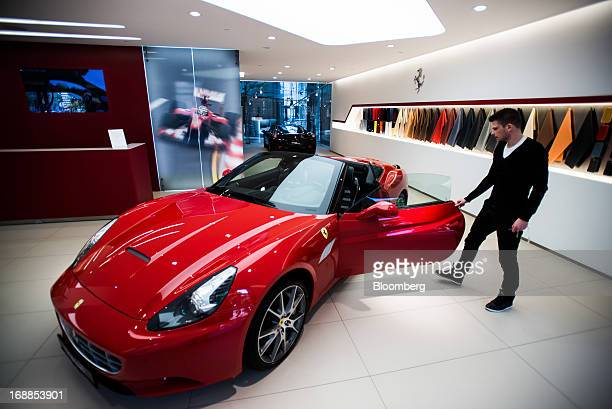 An employee examines a Ferrari California sports car in the showroom of an automobile dealership in Budapest Hungary on Wednesday May 15 2013 Ferrari...