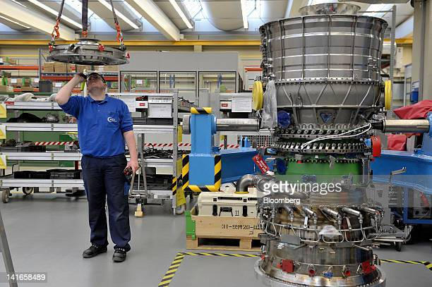An employee examines a part of a TP400D6 engine manufactured by MTU Aero Engines Holding AG for use on an Airbus SAS A400M military transporter...