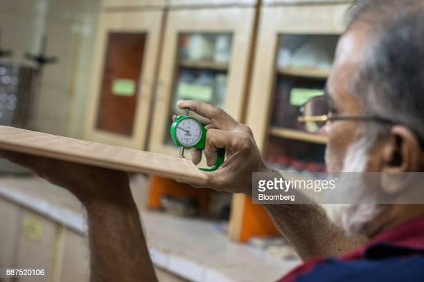 An employee examines a sample tile in the laboratory at the Shabbir Tiles Ceramics Ltd production facility in Karachi Pakistan on Wednesday Dec 6...