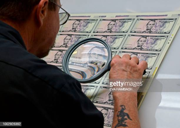 An employee examines a sheet of freshly printed 5 USD notes at the US Treasury's Bureau of Engraving and Printing in Washington DC July 20 2018 The...