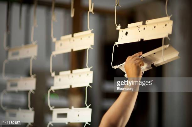 An employee examines dried powder coated metal parts at Staber Industries Inc in Groveport Ohio US on Thursday March 8 2012 The US Census Bureau is...