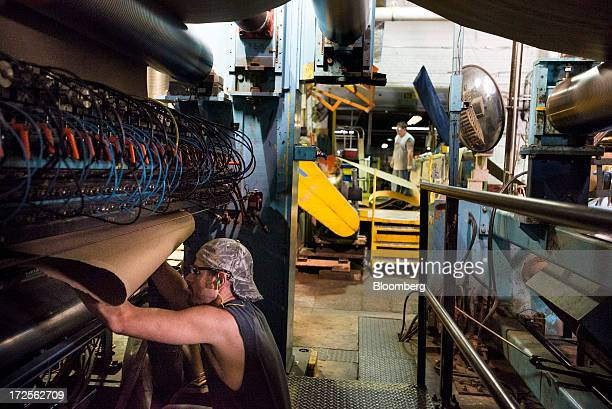 An employee feeds the end of a roll of paper through a cutting machine at Newark Recycled Paperboard Solutions in Baltimore Ohio US on Tuesday July 2...
