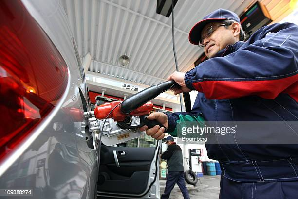 An employee fills a customer's tank at a gas station in Tokyo Japan on Thursday Feb 24 2011 Oil advanced for a sixth day in New York after reaching...