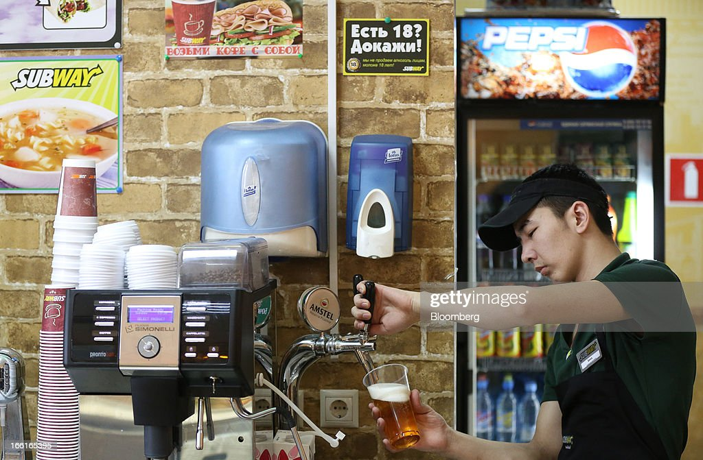 An employee fills a glass with Amstel beer inside a Subway fast food restaurant in Moscow, Russia, on Sunday, April 7, 2013. McDonald's, which virtually created the market for burgers and fries in the country and convinced Russians it's OK to eat with their hands, must fend off a growing challenge from rivals Burger King Worldwide Inc., Subway Restaurants, Yum! Brands Inc. and Wendy's Co. Photographer: Andrey Rudakov/Bloomberg via Getty Images