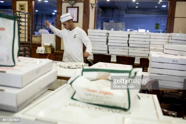 An employee fills a large number of Baklava orders at the famous Imam Cagdas Baklava shop during celebrations to mark the EidalAdha feast on August...