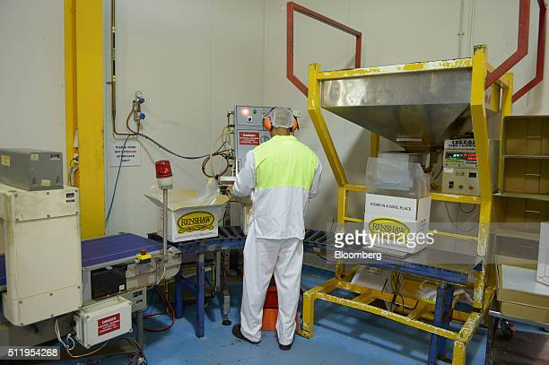 An employee fills boxes with Renshaw brand finely chopped peanuts at a Select Harvests Ltd processing facility in Melbourne Australia on Monday Feb...