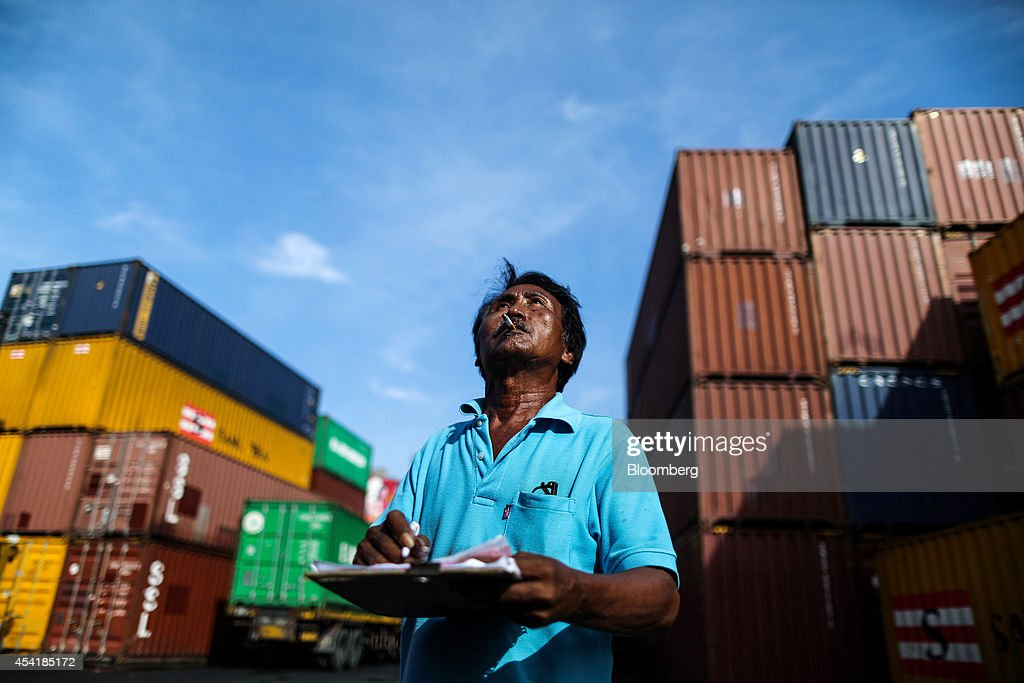 An employee fills in paperwork while smoking as containers sit stacked at the Custom Global Service Co. container depot in Bangkok, Thailand, on Monday, Aug. 25, 2014. Thailand's trade figures are scheduled for release on Aug. 27. Photographer: Dario Pignatelli/Bloomberg via Getty Images