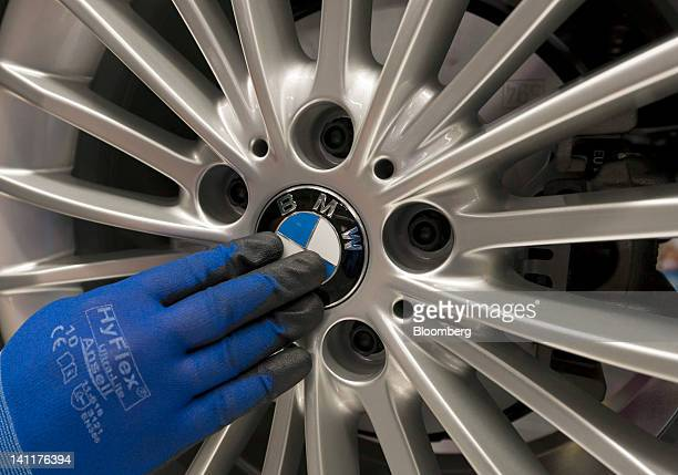 An employee fits a BMW cap to a alloy wheel hub on a Bayerische Motoren Werke AG 3series automobile as it travels along the production line at the...