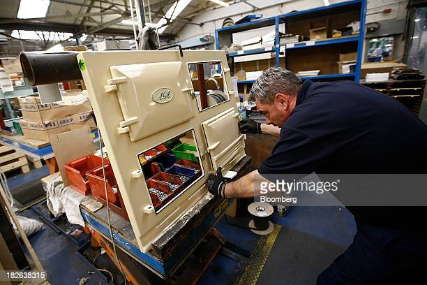 An employee fits a door to a cream AGA 3Oven Classic range cooker produced by AGA Rangemaster Plc during the manufacturing process at the company's...