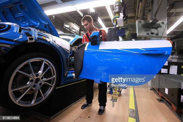 An employee fits a door to a Porsche 718 Cayman luxury automobile on the production line inside the Porsche AG factory in Stuttgart Germany on Friday...