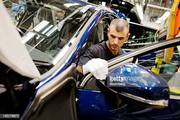 An employee fits a door to an automobile on the production line at the Volvo Car Corp plant in Gothenburg Sweden on Friday May 25 2012 Volvo Car Corp...