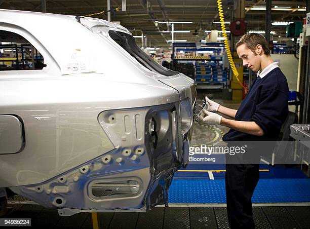 An employee fits a part to the back of a new Avensis automobile at Toyota's manufacturing plant in Derbyshire UK on Thursday Dec 18 2008 Toyota Motor...