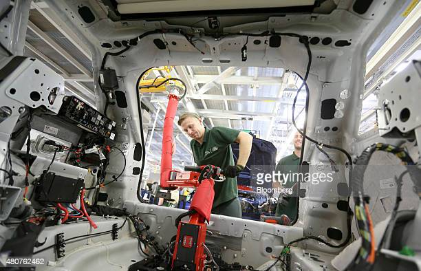 An employee fits a part to the inside of a Range Rover Sport SUV using a robotic arm at Tata Motors Ltd's Jaguar Land Rover vehicle manufacturing...