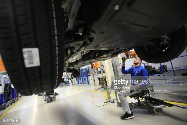 An employee fits a protective underbody shield to a Volkswagen Transporter T6 panel van inside the Volkswagen AG factory in Hanover Germany on...