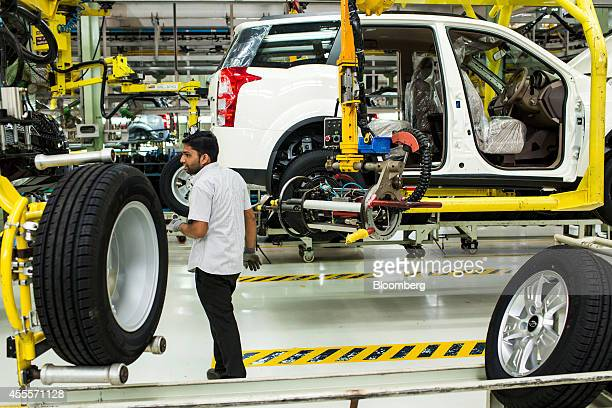 An employee fits a wheel to a Mahindra Mahindra Ltd XUV 500 sportutility vehicle on the production line at the company's facility in Chakan...