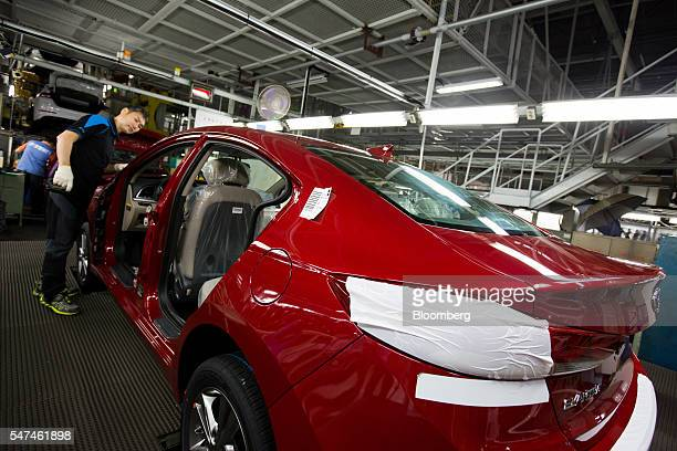 An employee fits a windscreen onto a Hyundai Motor Co. Elantra vehicle on the production line at the company's plant in Ulsan, South Korea, on...