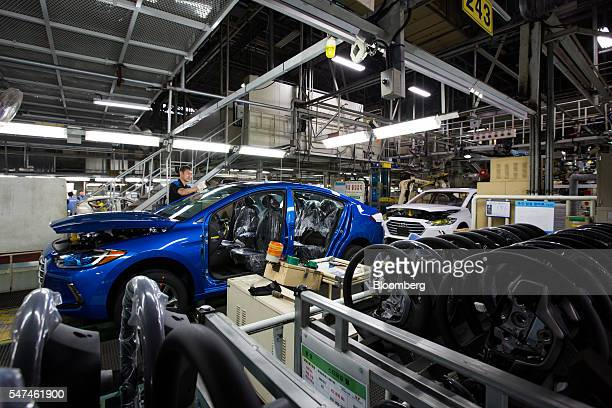 An employee fits a windscreen onto a Hyundai Motor Co. Elantra vehicle as steering wheels sit on the production line at the company's plant in Ulsan,...